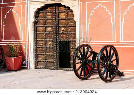 The old cannon near the wall and the openwork door in Jaipur City Palace Rajasthan India. Maharaja Residence. Indian architecture.