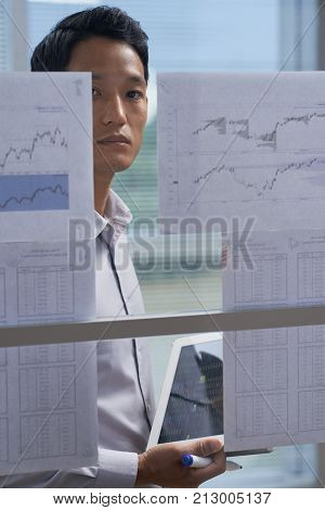 Unsmiling young entrepreneur working in financial department