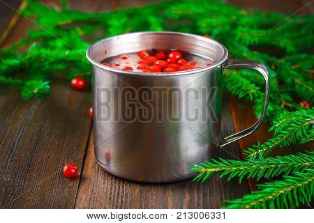Morse Or Tea From Cowberry In A Tin Mug, Surrounded By Fir Branches On A Wooden Table.