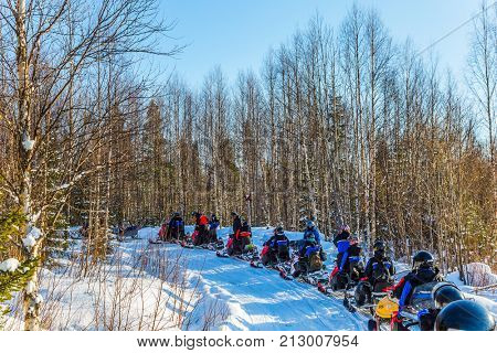 Tourist train from snowmobiles moves along the ice of a frozen river. Concept of active winter tourism. Snowmobiling