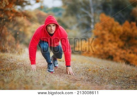 A Slim  Athletic Jogger Man At The Start Preparing To Run On The Bright Autumnal Forest Hill.