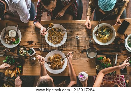 Group of happy friends having nice food and drinks enjoying the party and communication Top view of Family gathering together at home for eating dinner.