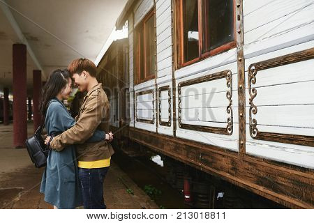 Vietnamese young couple hugging at train station