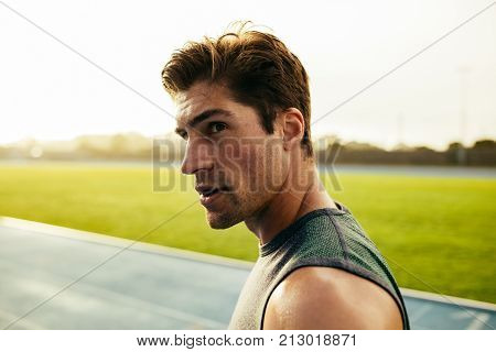 Closeup of a sprinter standing on a running track. Runner looking away standing on the track. poster