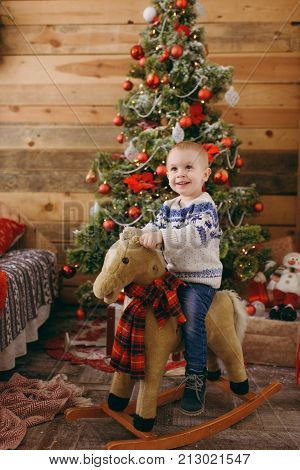 Happy Cute Little Baby Boy On Rocking Horse At Christmas Tree With A Toy, Dressed In Sweater And Jea