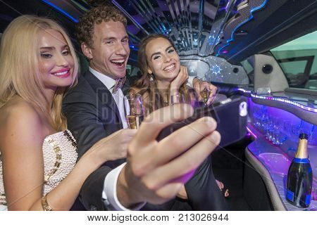 Celebrating by taking a selfie in a limousine by the young rich and famous, with champagne in their hands