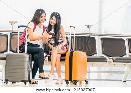 Two young Asian girl using smartphone check flight or web check-in sit at airport waiting seat together. Air travel lifestyle exciting summer vacation trip or mobile phone gadget application concept