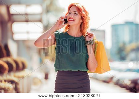 People, sale and consumerism concept - close up of woman with shopping bags and mobilphone.