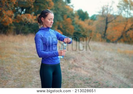 A Young Caucasian Athletic Woman Opens A Bottle With Water After Jogging.
