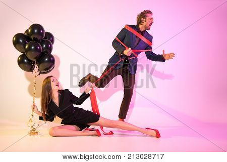 Girl Holding Man Bound With Ribbon