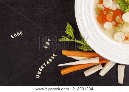 Fresh broth soup with vegetables and alphabet noodles on dark surface from above. Bouillon with words from noodles. Gastronomy. Lunch menu background.