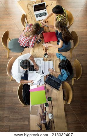 Top view group of teenage friends working in team with reports and laptop on wooden table