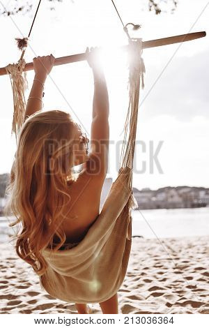 Perfect vacation. Rear view of attractive young woman in swimwear sunbathing while sitting in the hammock on the beach poster