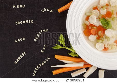 Alphabet Pasta and Vegetable Soup with noodle letters from above. Dark surface. Gastronomy background. Broth vegetable bouillon.