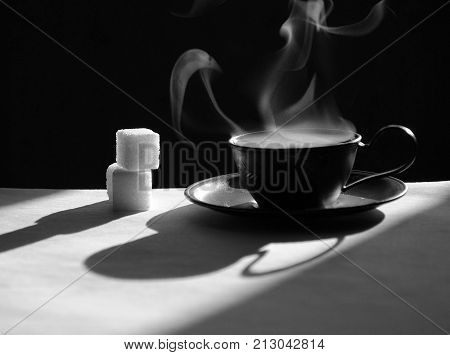 a cup of coffee with hot steam, a black and white still-life with coffee and sugar, a stylish still-life with coffee
