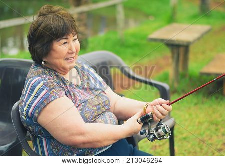 Old Woman Seated, Smiling, Fishing, Holding A Fishing Rod. B