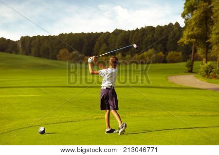 Boy golf player hitting by iron from fairway at golf course