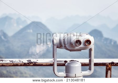 Vintage Toned Picture Of Tourist Binoculars Pointing At Karst Formations.
