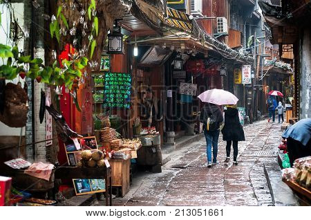 FENGHUANG CHINA - NOV 11 2014 - Tourists browse Fenghuang's local shops Hunan Province China