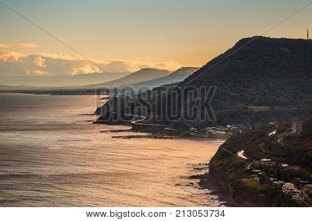 Aerial view of the Sea cliff bridge along Maddens Plains and the village of Coalcliff  near Sydney at sunset.