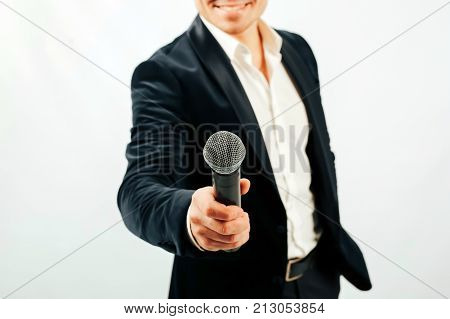 An anchorman with a microphone takes an interview on a white background. Man in a suit with a microphone on a white background.