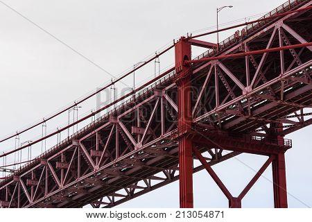Close-up Of Red Steel Beam Suspension Bridge Against Grey Sky