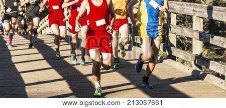 High school boys cross country race running over a wooden bridge at sunken meadow state park long island new york.