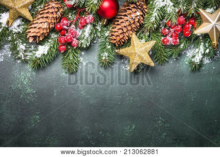 Christmas background. Snow Fir tree branch pine cones red and golden christmas decorations on green stone background. Top view copy space.