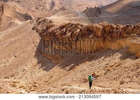 One unrecognized hiker on desert trail in Negev mountains Israel.