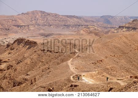 Unrecognized couple of hikers on scenic trail in Negev desert mountains Israel.