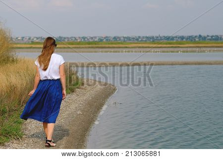 a woman in a blue skirt and a white shirt walking along the river