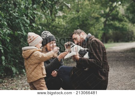 Happy family playing with dog fox terrier. Outdoor