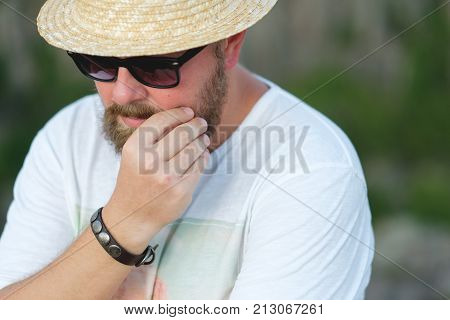 A hipster man in sunglasses and a straw hat with a beard.