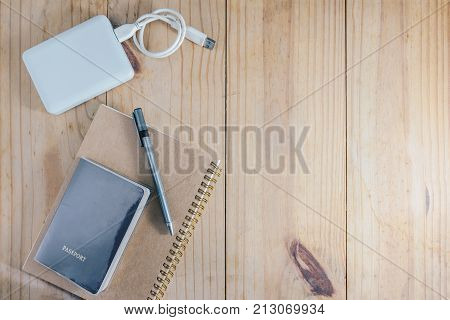 Top view of travel object : passport and gray pencil on brown notebook and white external harddisk on wooden table
