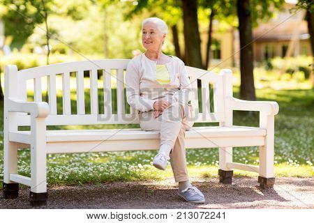 old age, retirement and people concept - happy senior woman sitting on bench at summer park