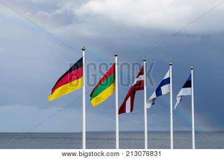 Estonian Finnish Lithuanian Latvian and German flags waving in the wind blue sky and rainbow in the background