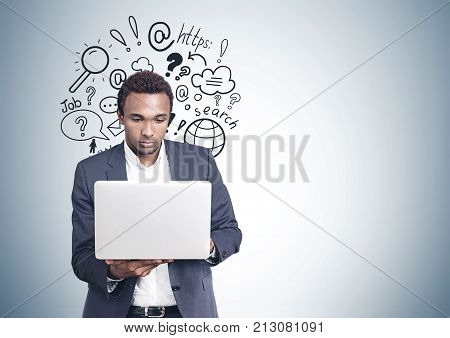 Portrait of a concentrated young African American businessman wearing a suit and looking attentively at his white laptop screen. An Internet search sketch on a gray wall. Mock up