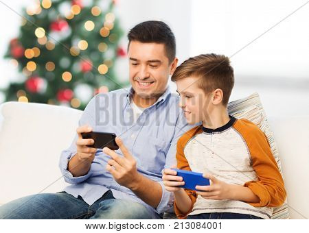 technology, family and people concept - happy father and son with smartphones texting message or playing game at home over christmas tree background