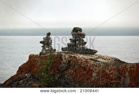 stone marker inukshuk on a lake shore poster