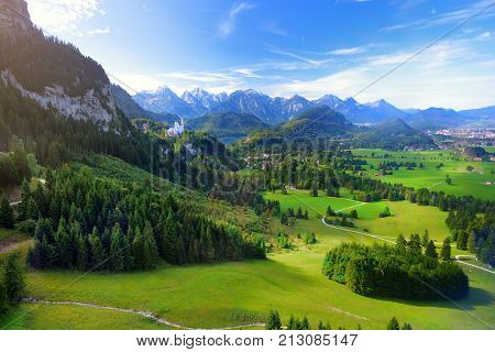 Famous Neuschwanstein Castle Visible In The Distance, Located On A Rugged Hill Above The Village Of