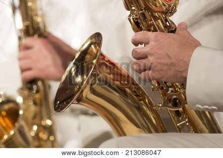 Close-up. A man in a white suit plays a saxophone in a jazz orchestra.