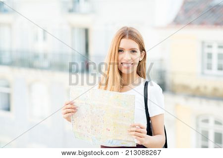 Cheerful redhead tourist visiting new city and using map. Happy attractive girl looking at camera while walking over strange city. Navigation concept