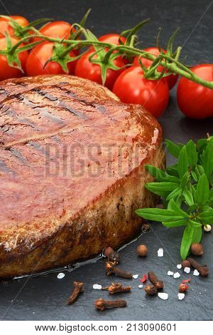 Grilled Beef Steak With Cherry Tomatoes And Spices On Black Stone Board