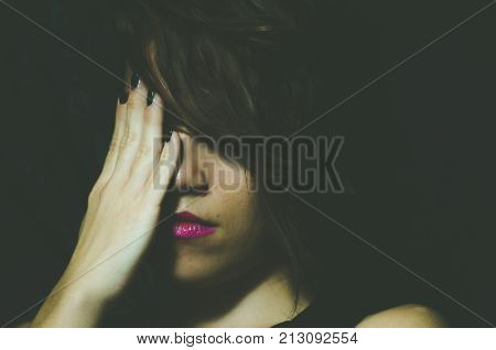 Young depressed woman feeling miserable and lonely cover her face with her hands in the dark room of her home