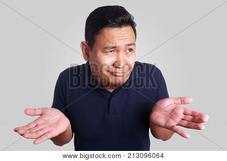 Photo image of funny Asian man with shrug shoulder up gesture showing i don't know or rejection