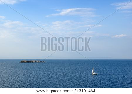 Seascape with sailing yacht and small island in sea