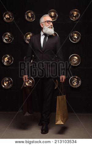 Fashion business man make a purchases. Beard fashion in modern life, rich old fashionable man walking after shopping with package and smile.