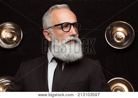 Pensive man in fashion glasses look away. Styling old man with a long white beard posing on the dark background in modern strict suit. Portrait of modern Santa Claus