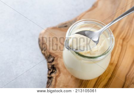 One glass jar with lemon or vanilla curd dessert with a spoon on a wooden board light stone table
