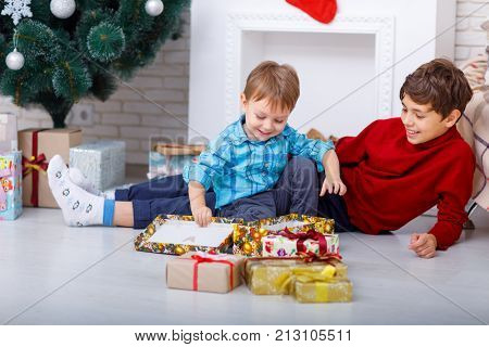 Portrait of charming brothers who sit on the floor at home next to New Year's gifts, the younger brother opens a gift.